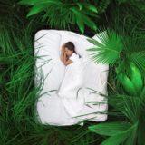 緑のジャングルの中のベッドで眠る女性