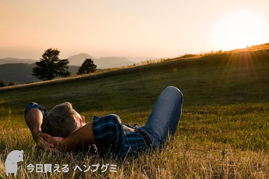 草原に寝そべって夕日を見る男性3