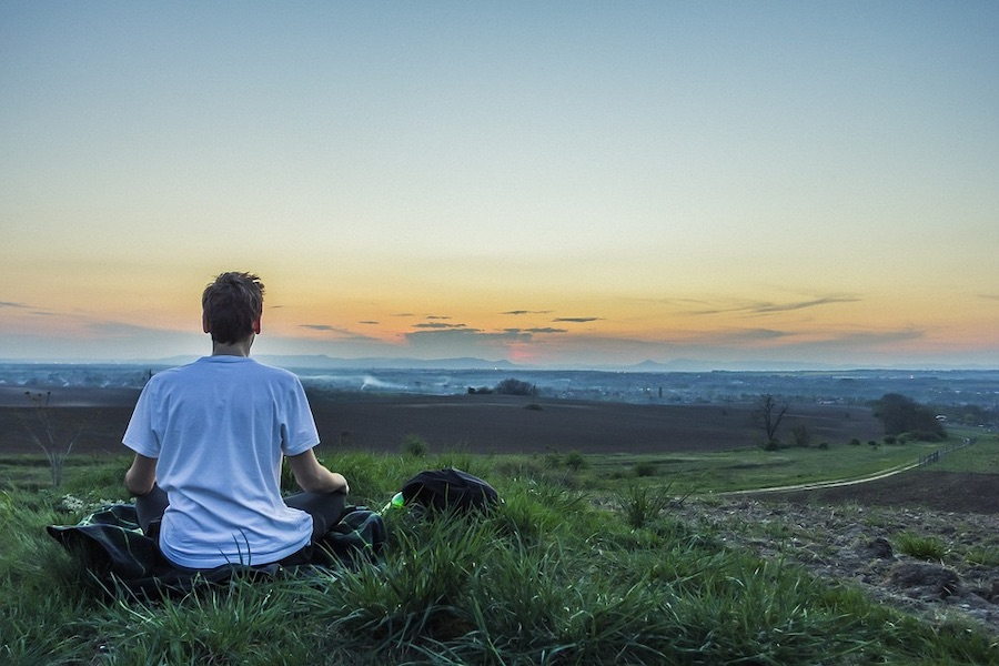 丘の上から爽やかな朝を見つめる男性
