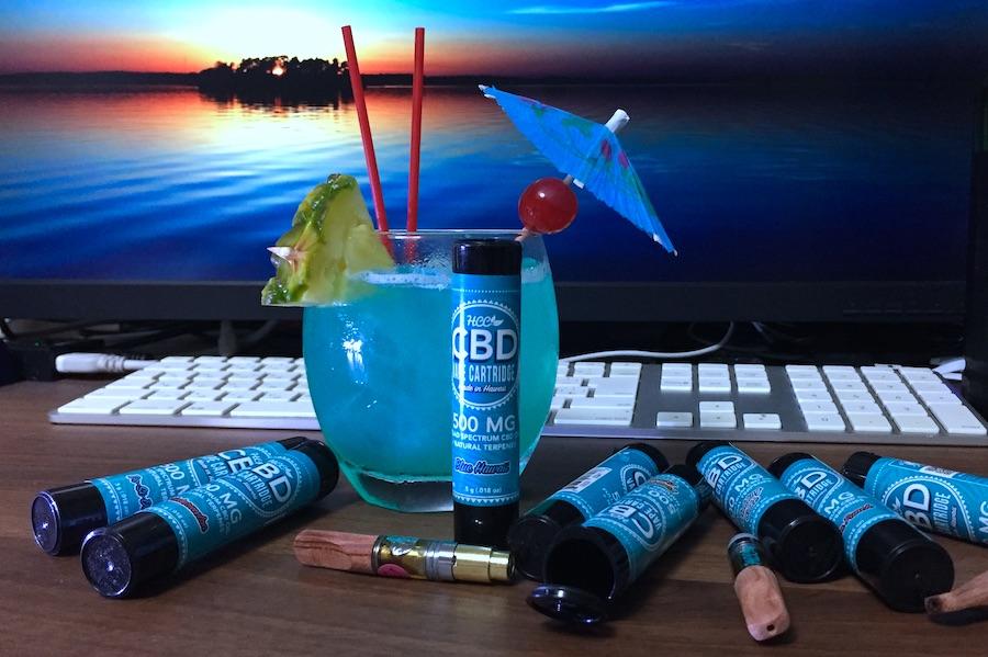 CBDを楽しみながらフレーバーを味わう HCC ハワイカンナビスケア 65%CBDカートリッジと一緒にカクテルブルーハワイを飲んでいる写真