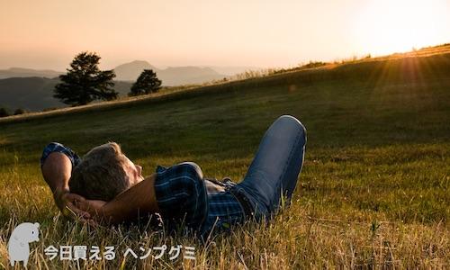 草原に寝そべって夕日を見る男性2