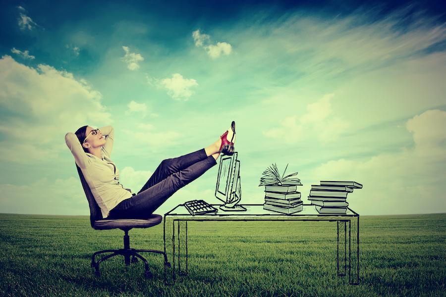 自然の中に置かれたオフィスチェアに座ってリラックスする女性