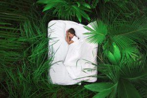 野外の緑の植物に囲まれたベッドで眠る女性