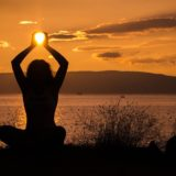 沈んでいく太陽を手に取るようなポーズの女性