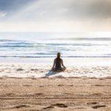 砂浜に座って海を見つめる女性