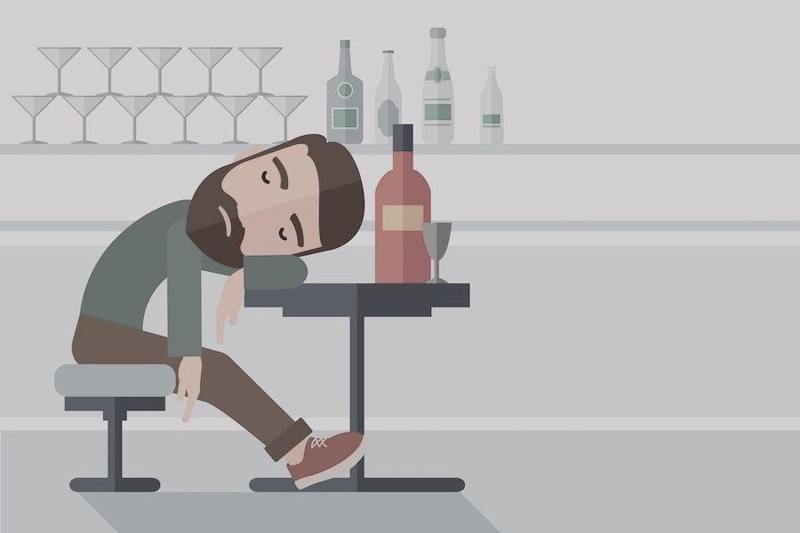 パブのテーブルに寄りかかって眠る男性