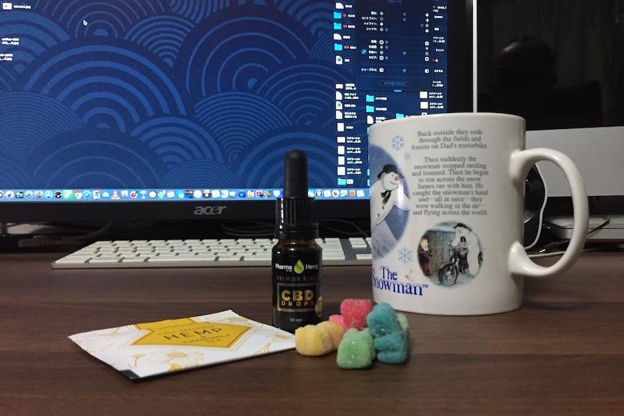 机の上のCBDオイルとヘンプティーとヘンプオイル入りグミ