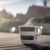 朝の屋外に置かれたコーヒーカップ