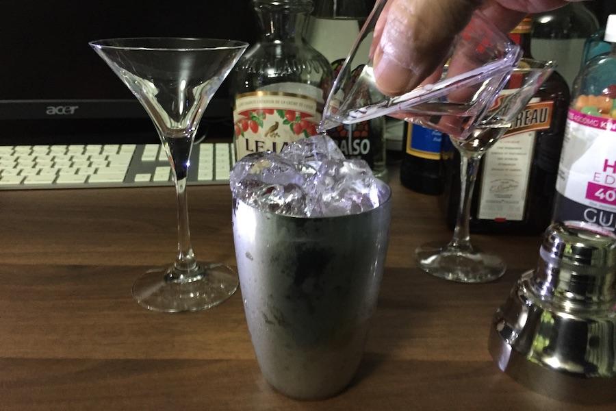 ウオッカを計量カップから氷の入ったシェーカーに注ぐ